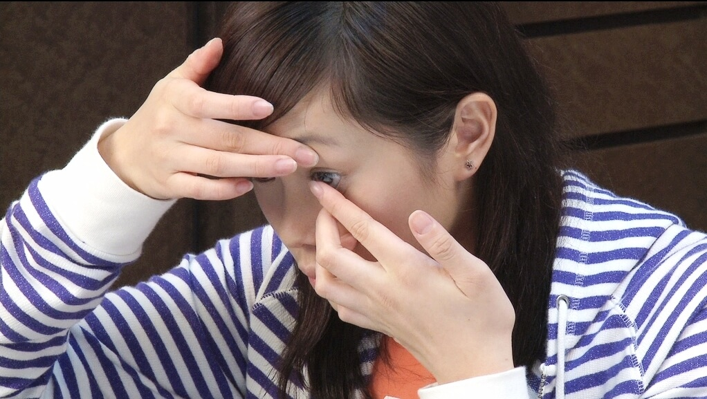 A woman putting in a contact lens.