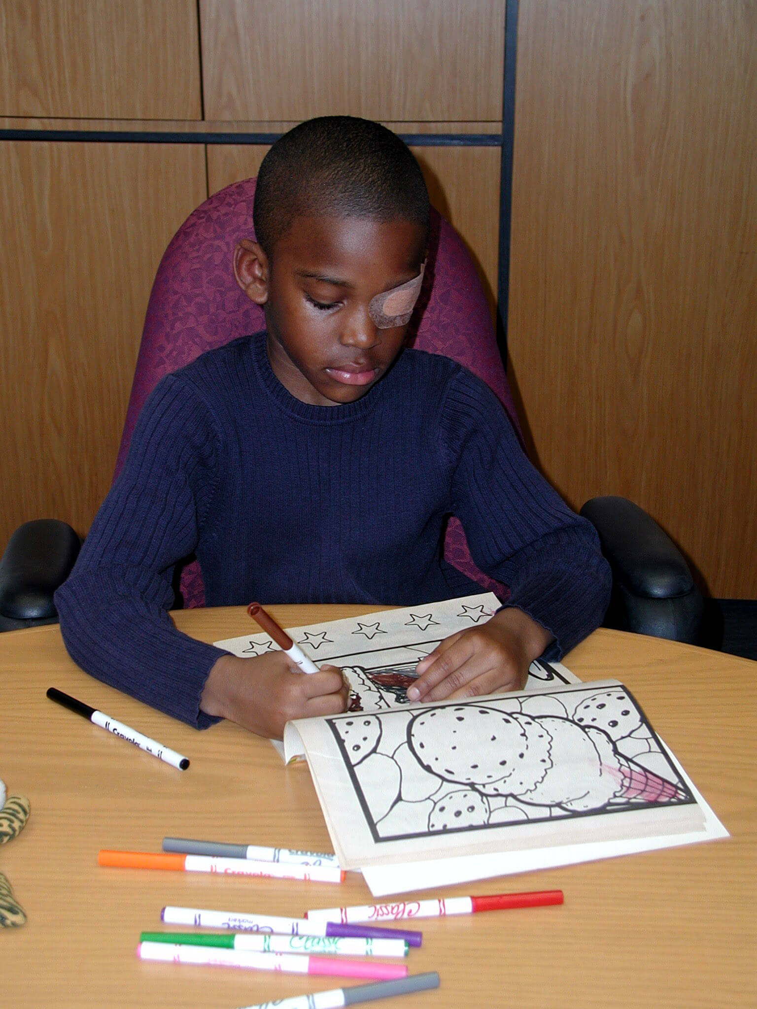 A child wearing an eyepatch while colouring in.