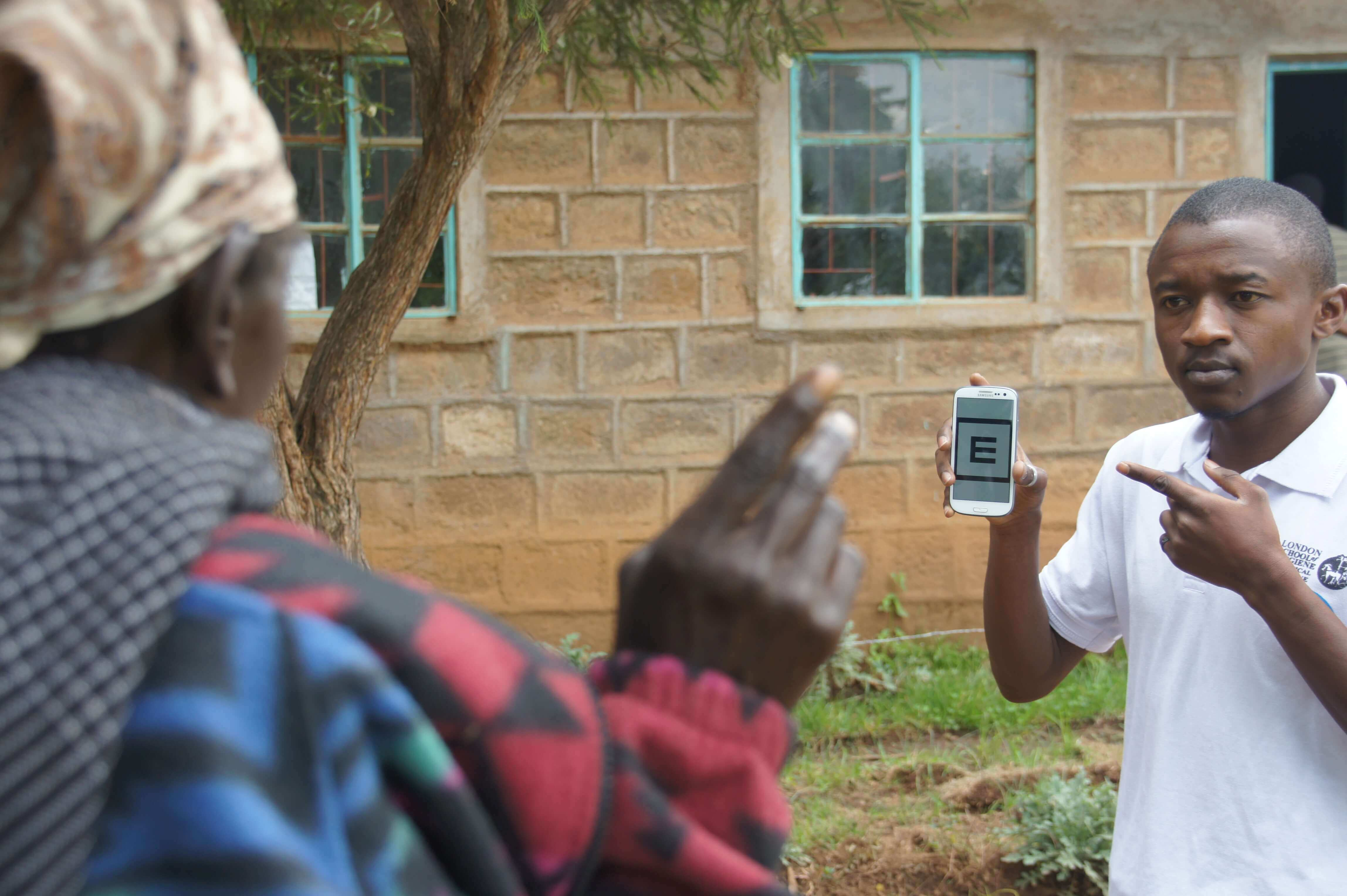 A healthcare worker in Kenya holding up a smartphone showing the Peek Acuity test, towards a woman with her back to the camera, pointing to indicate the direction that the letter E on the screen is facing.