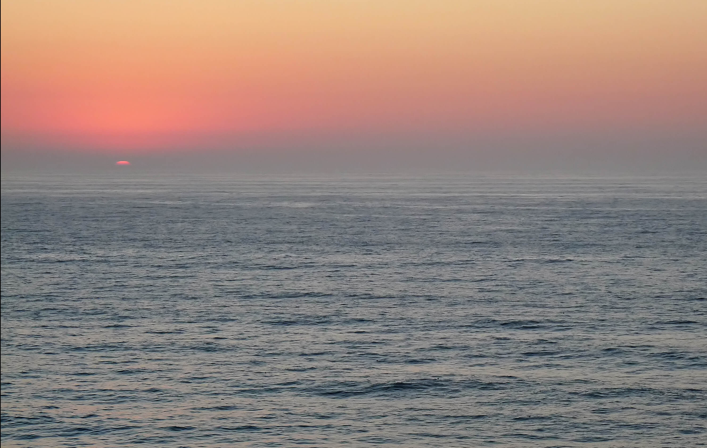 A view over an empty, calm sea to the hazy horizon at sunrise (or sunset - I can't tell!).