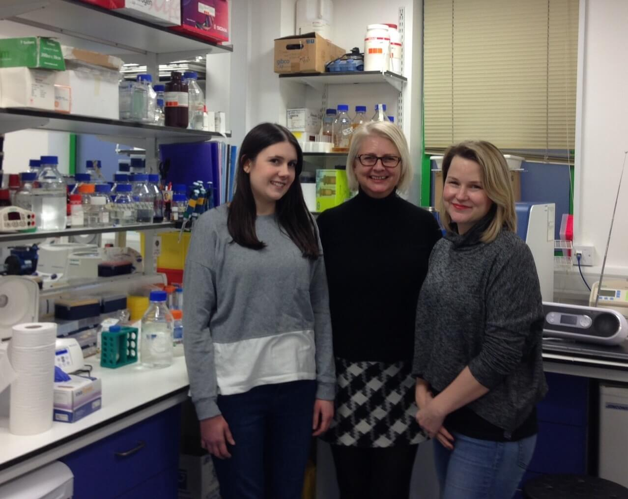 The research team pictured standing together in the lab.