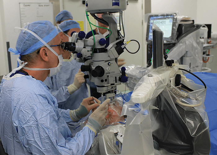 Prof MacLaren looks down a miscrocope during surgery.