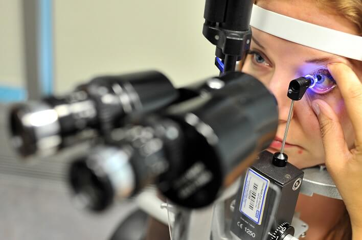 A person having an eye examination with an instrument to look through the pupil to the retina at the back of the eye.