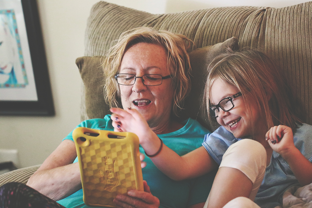 Older woman and grandchild playing on tablet