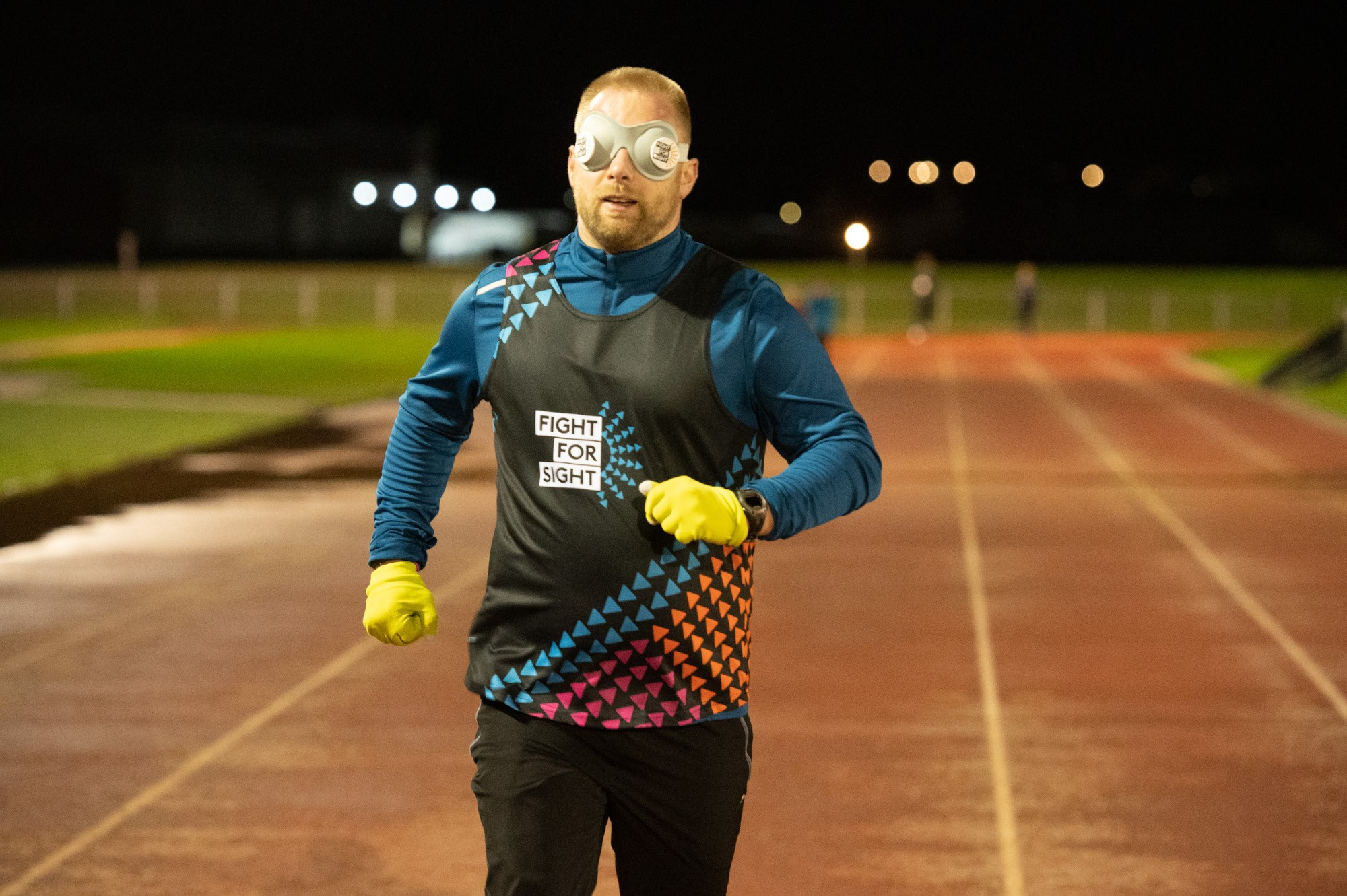 A man running on a track while blindfolded.