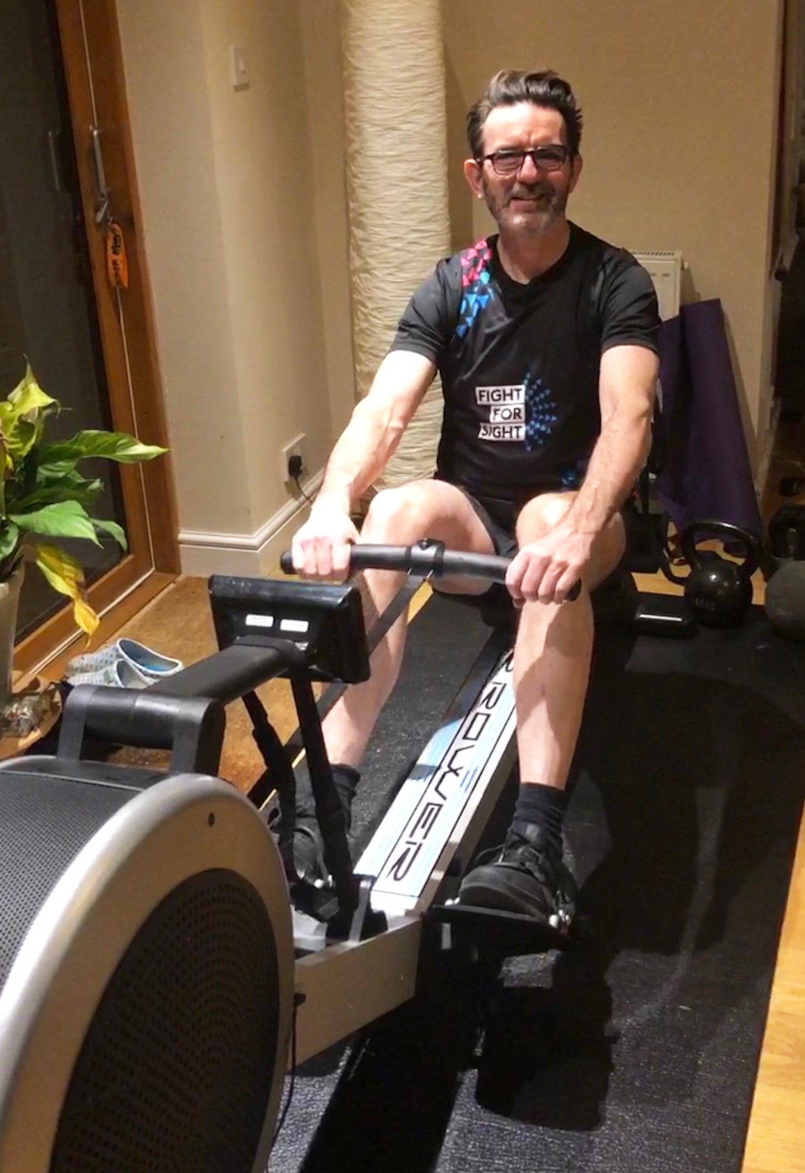 A man wearing a Fight for Sight running vest, on a rowing machine in his home.