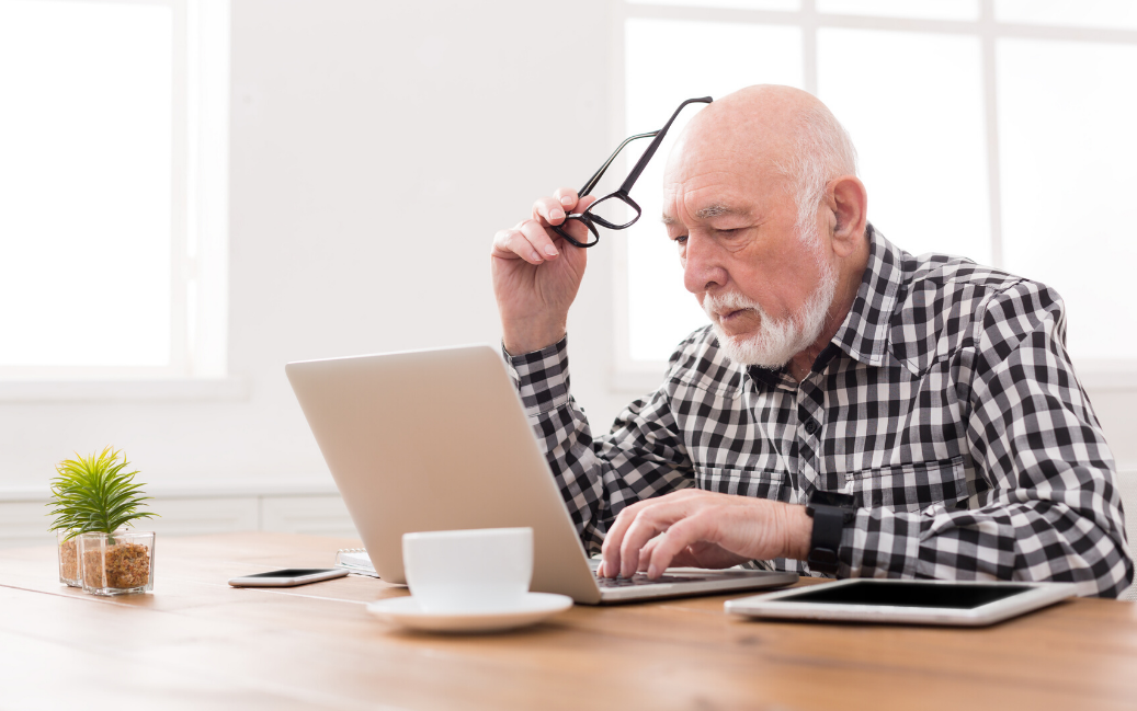 An older man sitting at his computer, holding his glasses and looking concerned.