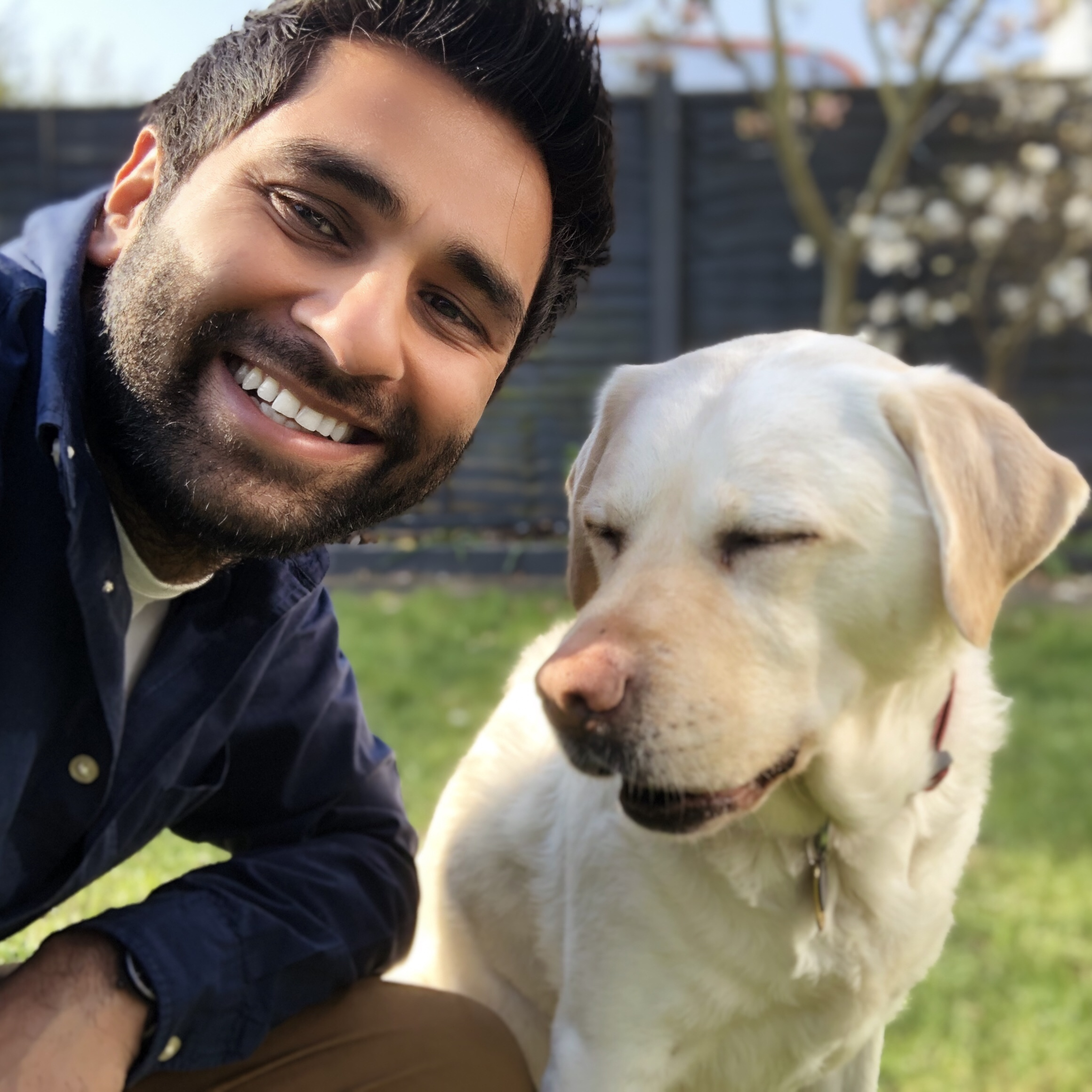 A picture of a man smiling at the camera next to his guide dog.