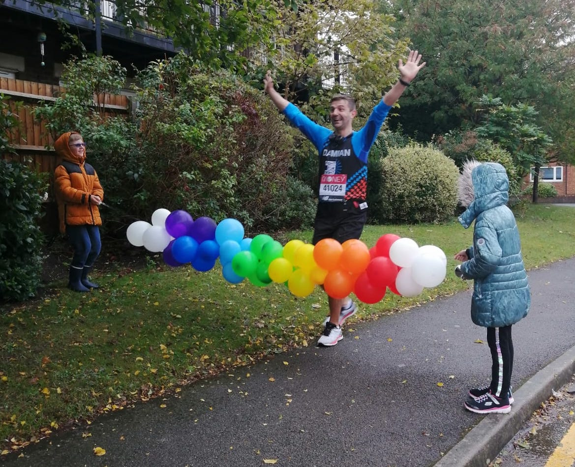 A man running in the rain towards a finish line of balloons being held up by a young boy and a woman wearing coats.