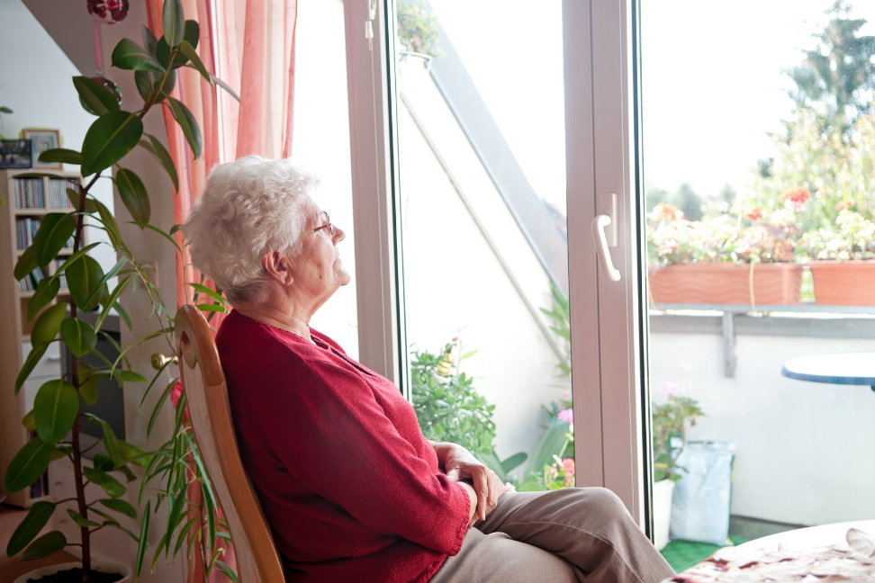 An elderly woman sitting in a chair looking out the window.