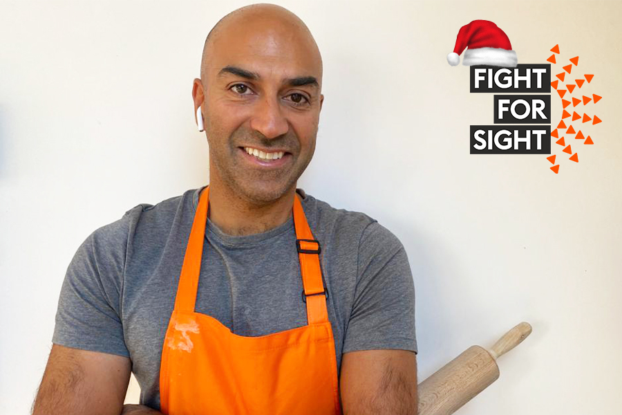 Amar Latif posing in an orange apron with a rolling pin in his hand.