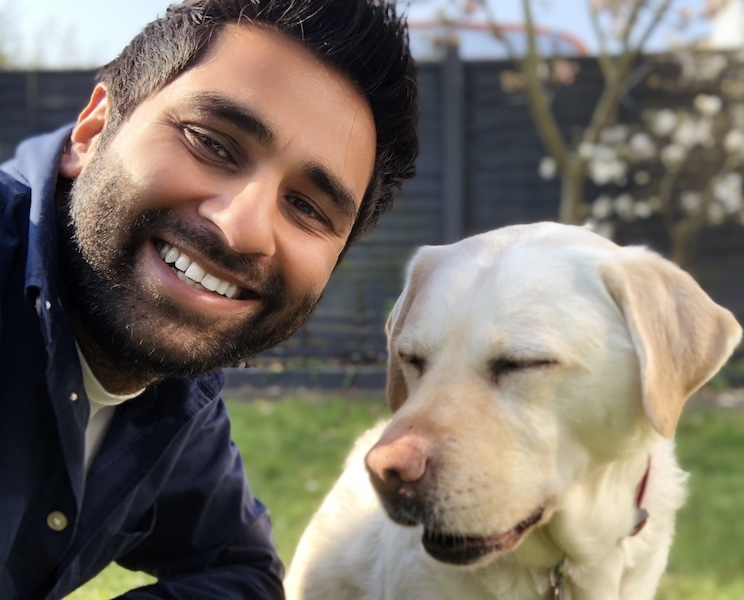 A man and his guide dog smiling at the camera.